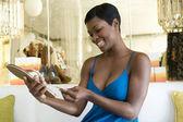 Frau schaut preisschild auf jewelled flip-flops — Stockfoto