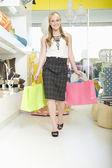 Weibliche käufer geht mit einkaufstaschen — Stockfoto