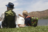 Grandfather And Grandson Sit With Map At Lakeside — Stock Photo