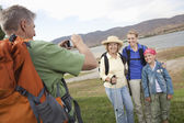 Man Photographs Mother, Daughter And Granddaughter Lakeside — Stock Photo