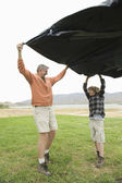 Father And Son Holding Groundsheet — Stok fotoğraf