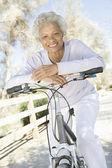 Senior Woman Leans On Handlebars Of Mountain Bike — Foto de Stock