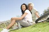 Moeder en dochter zittend op het gras in park — Stockfoto