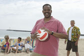 Man Holding Volley Ball At Beach With Friends Grouped Behind — Stock Photo
