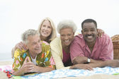 Multiethnic Friends Lying Down On Stomach At Beach — Stock Photo