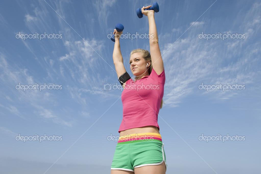针对多云的天空在听音乐的同时举重运动年轻女子的低