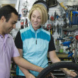 Bike shop assistant helping female cyclist — Stock Photo