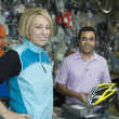 Female cyclist buying helmet at bike shop — Stock Photo #21927787
