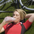 Female Cyclist Lying On Grass Drinking Water — Stock Photo