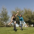 Female Friends Riding Bicycles In Park — Stock Photo
