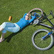 Woman With Bicycle Lying On Grass In Park — Stock Photo #21928017