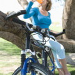 Female Bicyclist Drinking Water By Tree — Stock Photo