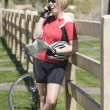 Stock Photo: Cyclist with her bike leaning on fence while using cell phone