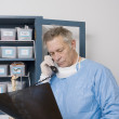 Doctor Analyzing X-Ray Report While Using Landline Phone - Stock Photo
