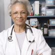 Senior Female Doctor With Arms Crossed In Clinic — Stock Photo