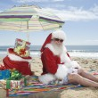 Santa Claus Sitting Under Parasol With Gifts On Beach — Stock Photo