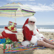 Stock Photo: Santa Claus Sitting Under Parasol With Gifts On Beach