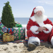 Santa Claus With Presents And Tree Sitting On Beach — 图库照片