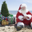 Santa Claus With Presents And Tree Sitting On Beach — Stock Photo