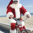 Santa Claus Cycling By Beach — Stock Photo