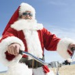 Santa Claus Cycling Against Blue Sky — Stock Photo #21928613