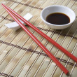 Soy Sauce With Chopsticks On Mat — Photo