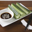 Soy Sauce With Cucumber Slices And Chopsticks On Table - Stock Photo
