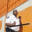 Stock Photo: Security Guard With Baton Using Walkie Talkie