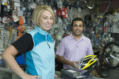 Female cyclist buying helmet at bike shop — Stock Photo