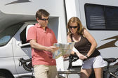 Couple Looking At Roadmap Standing Against RV — Stock Photo