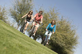 Man with two women cycling in park — Stock Photo