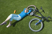 Woman With Bicycle Lying On Grass In Park — Stock Photo