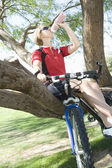 Female Bicyclist Sitting On Tree While Drinking Water — Stock Photo