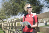Bicyclist Holding Roadmap While Leaning On Fence — Stockfoto