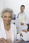 Doctor Sitting With Documents And Colleague Standing In Background — Stock Photo