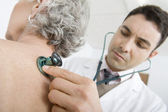 Doctor Checking Patient's Back Using Stethoscope — Stockfoto
