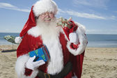 Father Christmas Stands With His Sack On Beach — Stock Photo