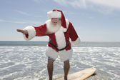 Father Christmas Surfboards At The Water's Edge — Stock Photo