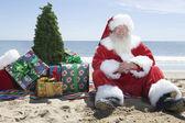 Mikołaj z prezentami i drzewa siedzi na plaży — Zdjęcie stockowe