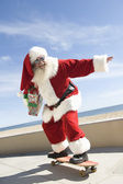 Santa Claus Skateboarding With Gift In Hand — Stock Photo