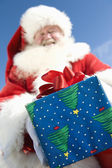 Santa Claus Giving A Present — Stockfoto