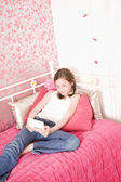 Young Girl In Bedroom Playing Handheld Game — Stock Photo