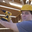 Man Drilling On A Wooden Beam At Site — Stock Photo #21930091