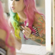 Reflection of a young woman in mirror applying lipstick — Stock Photo #21930555