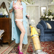 Stock Photo: Woman in bathrobe smoking cigarette while cleaning living room with vacuum cleaner