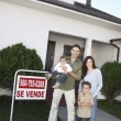 Family Standing In Front Of House For Sale - Stock Photo