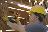 Workman Drilling On A Wooden Beam At Site — Stock Photo