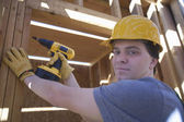Man Drilling On A Wooden Beam At Site — Stock Photo