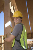 Laborer positioning plank of wood — Stockfoto