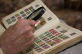 Man Examining An Old Stamp Book — Stockfoto